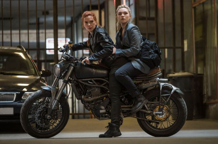 Natasha Romanoff (Scarlett Johansson) and Yelena Belova (Florence Pugh) escaping from their enemies in Black Widow on a motorcycle..